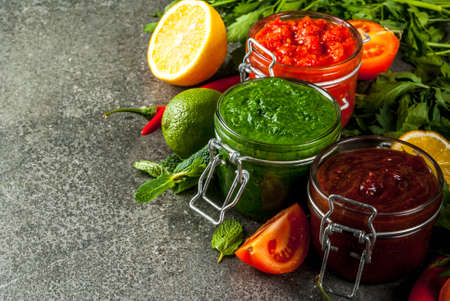 Indian traditional food, Set of three chutney for Chaat and Sev Puri - sweet date-tamarind, cilantro-mint green and red chilli garlic, On dark stone background, copy space
