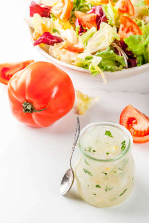 Classic salad dressing, homemade ranch dressing with olive oil herbs and lemon, with fresh vegetables on white marble table, copy space Standard-Bild