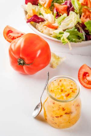 Classic Italian vinaigrette salad dressing, with fresh vegetables on white marble table, copy space Standard-Bild
