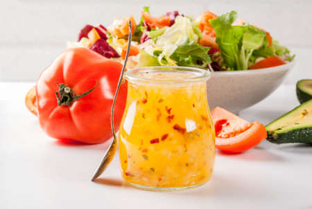 Classic Italian vinaigrette salad dressing, with fresh vegetables on white marble table, copy space Stock fotó