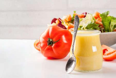 古典的な蜂蜜マスタードサラダドレッシング、白い大理石のテーブルに新鮮な野菜、コピースペース