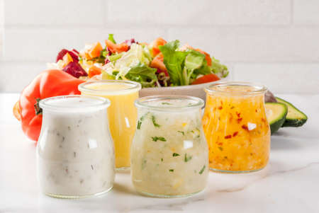 Set of classic salad dressings - honey mustard, ranch, vinaigrette, lemon & olive oil,  on white marble table, copy space Archivio Fotografico
