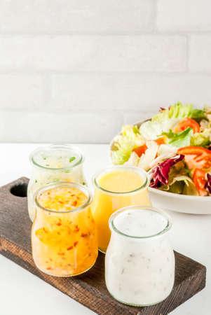 Set of classic salad dressings - honey mustard, ranch, vinaigrette, lemon & olive oil,  on white marble table, copy space Standard-Bild
