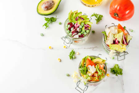 Fresh salads in jar with fresh vegetables and healthy dressings,  on white marble table, copy space