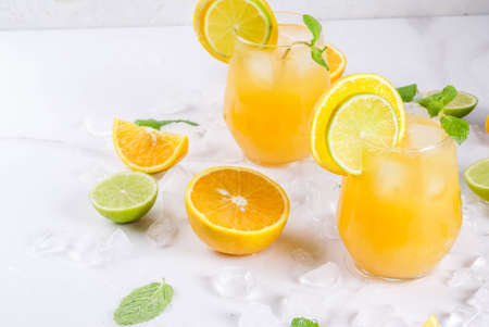 Vitamin summer refreshing drinks. Citrus punch with oranges and lime, with mint sprigs, chilled with ice. On a white marble table, with ingredients, copy space
