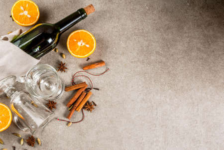 Christmas hot drinks recipes, Set of ingredients for mulled wine: wine bottle, glass cups, spices, orange. Gray stone background, copy space top view Standard-Bild