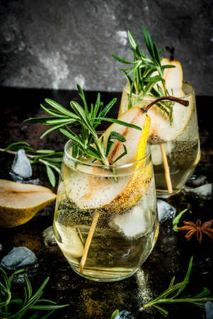 Alcohol drink, Sweet pear cocktail with rum, liquor, anise and rosemary, On a black rusty metallic background, copy space Standard-Bild