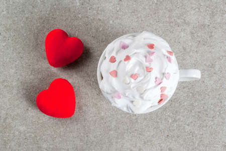 Romantic background, Valentines day. Cup for coffee or hot chocolate, with whipped cream and sweet hearts, with two plush red hearts,  copy space top view