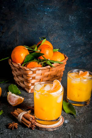 Spicy winter tangerine Cocktail with vodka, fresh tangerines, cinnamon and anise, on dark background, copy space
