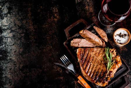 Gegrilde biefstuk met kruiden op grillpan bord, met en rode wijnglas. Ruimte bovenaanzicht kopiëren