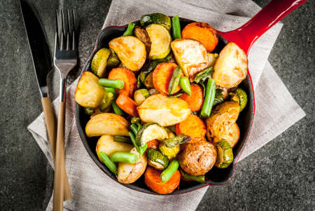 Skillet with  fried seasonal autumn vegetables (zucchini, potatoes, carrots, beans), on black stone table copy space top view