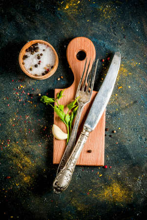Cooking food concept, spices, herb and oil for preparing dinner, with cutting board, table knife and fork, copy space top view Standard-Bild