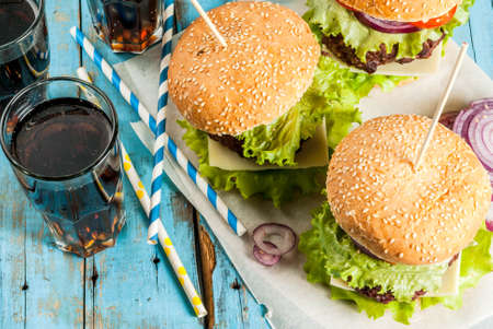 Picnic, Fast food. Unhealthy food. Delicious Fresh Tasty Burgers with Beef Cutlet, fresh Vegetables and Cheese on old rustic blue wooden table with sweet soda water. Copy space Standard-Bild