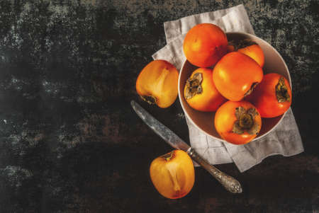Delicious raw ripe persimmon fruit on dark rusty metal background copy space top view Standard-Bild