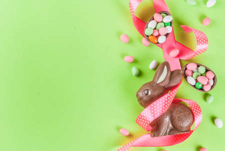 Easter holiday greeting card background, with chocolate easter bunny, candy eggs, quail eggs and festive ribbon, copy space top view Standard-Bild