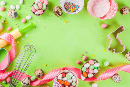 Sweet baking concept for Easter, cooking background with baking - with a rolling pin, whisk for whipping, cookie cutters, sugar sprinkling, flour. Light green background, top view copy space