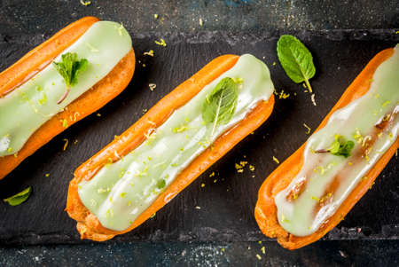 Traditional French dessert. Mojito Eclairs with lime zest and mint leaves, on dark blue background, copy space top view