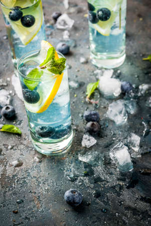 Summer refreshment drinks, Blueberry Lemonade or mojito cocktail with lemon, fresh blueberries and mint, sdark blue stone background copy space Standard-Bild