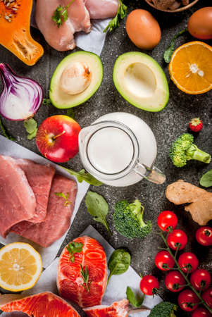 Healthy diet background. Organic food ingredients, superfoods: beef and pork meat, chicken filet, salmon fish, beans, nuts, milk, eggs, fruits, vegetables. Black stone table, copy space top view Standard-Bild
