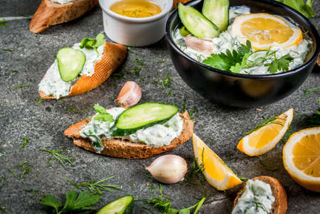 Traditional Caucasian and Greek food. Sauce tzatziki with ingredients - cucumber, lemon, parsley, dill, garlic. On a dark stone table. With sandwiches and baguette. Copy space