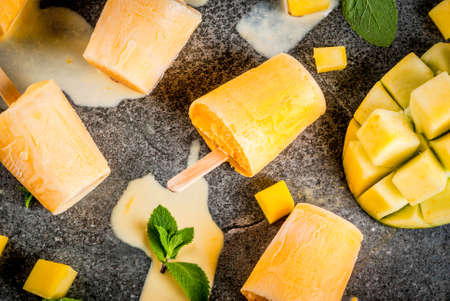 Ice cream, popsicles. Organic dietary foods, desserts. Frozen mango smoothie, with mint leaves and fresh mango fruit, on black stone table. Copy space  top view Standard-Bild