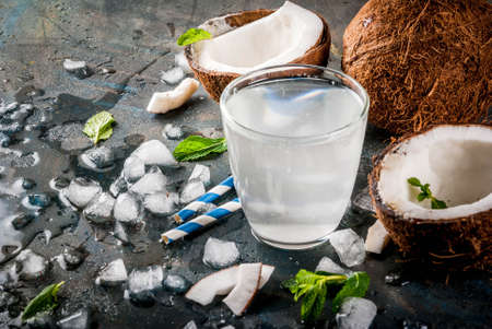Healthy food concept.  Fresh Organic Coconut Water with coconuts, ice cubes and mint, on rusty dark blue background, copy space Stok Fotoğraf