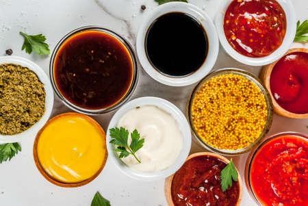 Ensemble de différentes sauces - ketchup, mayonnaise, barbecue, soja, teriyaki, moutarde, pentes de céréales, pesto, adzhika, chutney, tkemali, sauce à la grenade sur fond de marbre blanc. Espace de copie vue de dessus