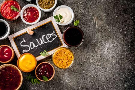 Set van verschillende sauzen - ketchup, mayonaise, barbecue, soja, teriyaki, mosterd, graanheuvels, pesto, adzhika, chutney, tkemali, granaatappelsaus op zwarte stenen achtergrond. Kopieer ruimte bovenaanzicht Stockfoto