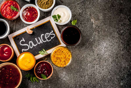 Zestaw różnych sosów - keczup, majonez, barbecue, sojowy, teriyaki, musztarda, zbożowe wzgórza, pesto, adzika, chutney, tkemali, sos granatowy na czarnym tle kamienia. Skopiuj widok z góry przestrzeni