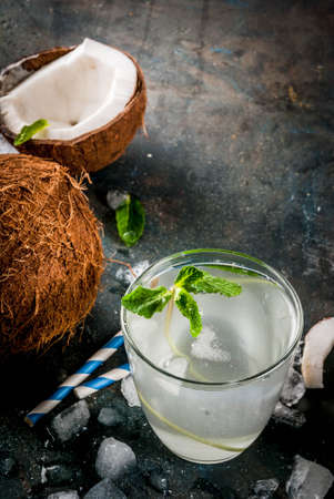 Healthy food concept.  Fresh Organic Coconut Water with coconuts, ice cubes and mint, on rusty dark blue background, copy space Stock Photo