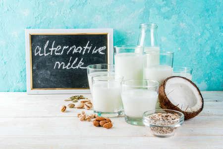 Veganistisch alternatief voedsel, set van verschillende niet-zuivelmelk - rijst, kokosnoot, amandelen, pistache, sesam, pompoenpitten, soja, noten, havermout, op lichtblauwe achtergrond, kopie ruimte