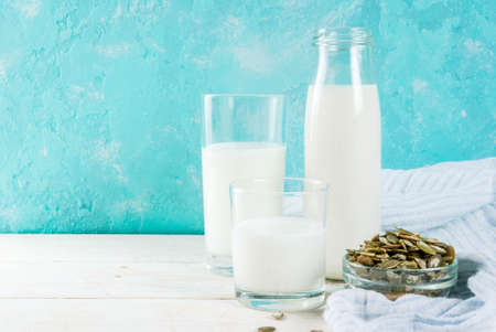 Vegan alternative food, pumpkin seeds non-dairy milk on light blue background, copy space