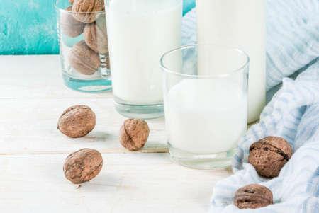Vegan alternative food, walnut non-dairy milk on light blue background, copy space