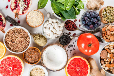 Set of organic healthy diet food, superfoods - beans, legumes, nuts, seeds, greens, fruit and vegetables.. white background copy space.