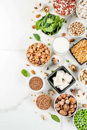 Zdrowa dieta wegańska żywność, wegetariańskie źródła białka: tofu, wegańskie mleko, fasola, soczewica, orzechy, mleko sojowe, szpinak i nasiona. Widok z góry na białym stole.