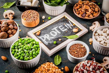 Alimenti vegani dietetici, fonti proteiche vegetali: tofu, latte vegano, fagioli, lenticchie, noci, latte di soia, spinaci e semi. Vista dall'alto sul tavolo bianco. Archivio Fotografico - 94056288