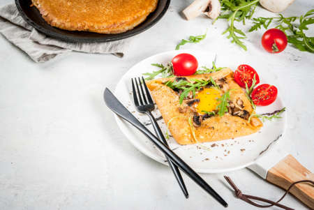 French cuisine. Breakfast, lunch, snacks. Vegan food. Traditional dish galette sarrasin. Crepes with eggs, cheese, fried mushrooms, arugula leaves and tomatoes. On a white concrete table. Copy space Stock Photo