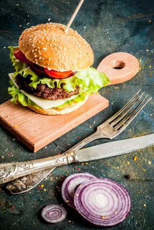 Fast food. Unhealthy food. Delicious Fresh Tasty Burgers with Beef Cutlet, fresh Vegetables and Cheese on dark blue concrete background. Copy space