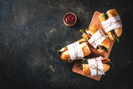 Fresh baguette sandwich with bacon, cheese, tomatoes and spinach, dark blue background copy space top view