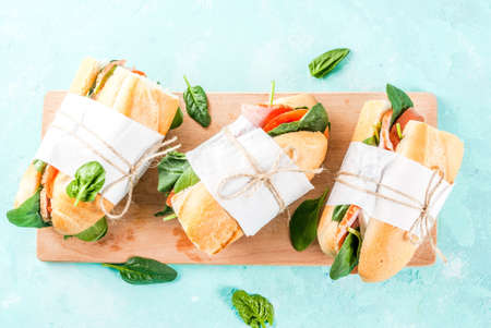 Fresh baguette sandwich with bacon, cheese, tomatoes and spinach, light blue background copy space top view