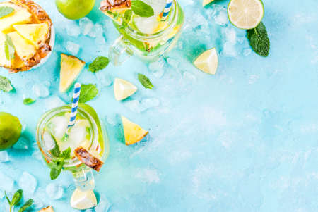 Tropical drink,  Pineapple mojito or lemonade with fresh lime and mint  light blue background, copy space top view Stok Fotoğraf
