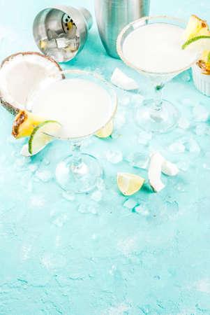 トロピカルドリンク、冷凍ピナコラーダ、テキーラ、パイナップルジュースとライム、ライトブルーの背景、コピースペースと冷凍ココナッツパイ 写真素材