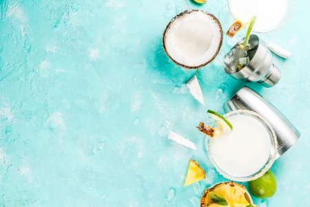トロピカルドリンク、冷凍ピナコラーダ、テキーラ、パイナップルジュースとライム、ライトブルーの背景、コピースペーストップビューと冷凍ココナッツパイナップルマルガリータ 写真素材 - 94384324