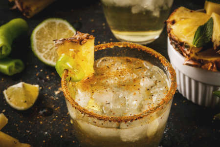 Mexican beverage, spicy margarita cocktail with pineapple and jalapeno and lime, dark blue background copy space