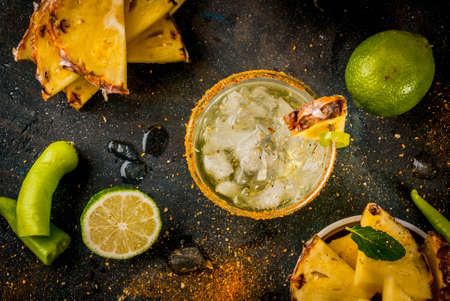 Mexican beverage, spicy margarita cocktail with pineapple and jalapeno and lime, dark blue background copy space top view