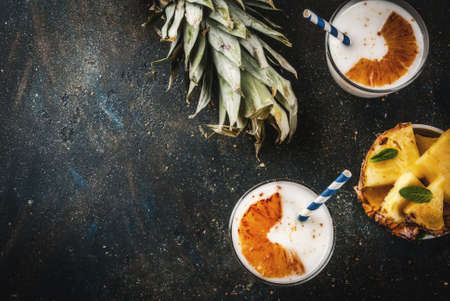 Indian food and drink, Caramelized Pineapple Lassi cocktail, dark blue background copy space top view Stock Photo