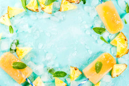 Homemade Pineapple Popsicles on Ice with fresh Pineapple slices and mint, on light blue background copy space top view frame