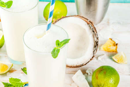 Tropical cocktail, pina colada, pineapple and coconut mojito or smoothies, with lime and mint, on a light blue background copy space