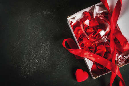Valentines day concept, white wrapped gift box with red ribbon, with rose flower petals in wine glass, with red candle, on dark stone background, copy space top view