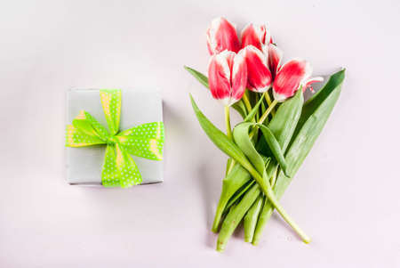 Spring holidays concept. Flowers tulips on white background with gift box. Copy space and top view for greeting card.